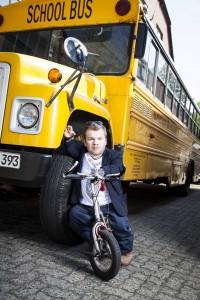 Michel auf seinem Roller, angelehnt an einen alten gelben Schulbus. © Anna-Lena Ehlers